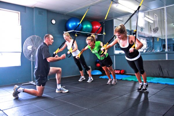 Women taking part in suspension training as part of waist shaping programme
