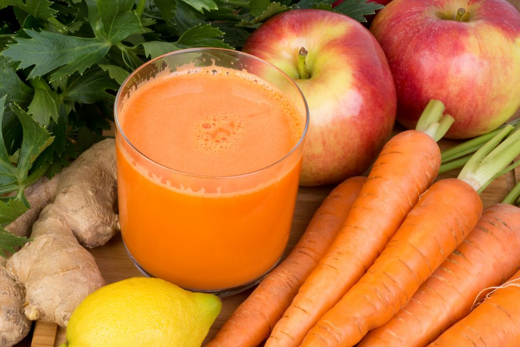 Glass of carrot juice plus carrots and apples