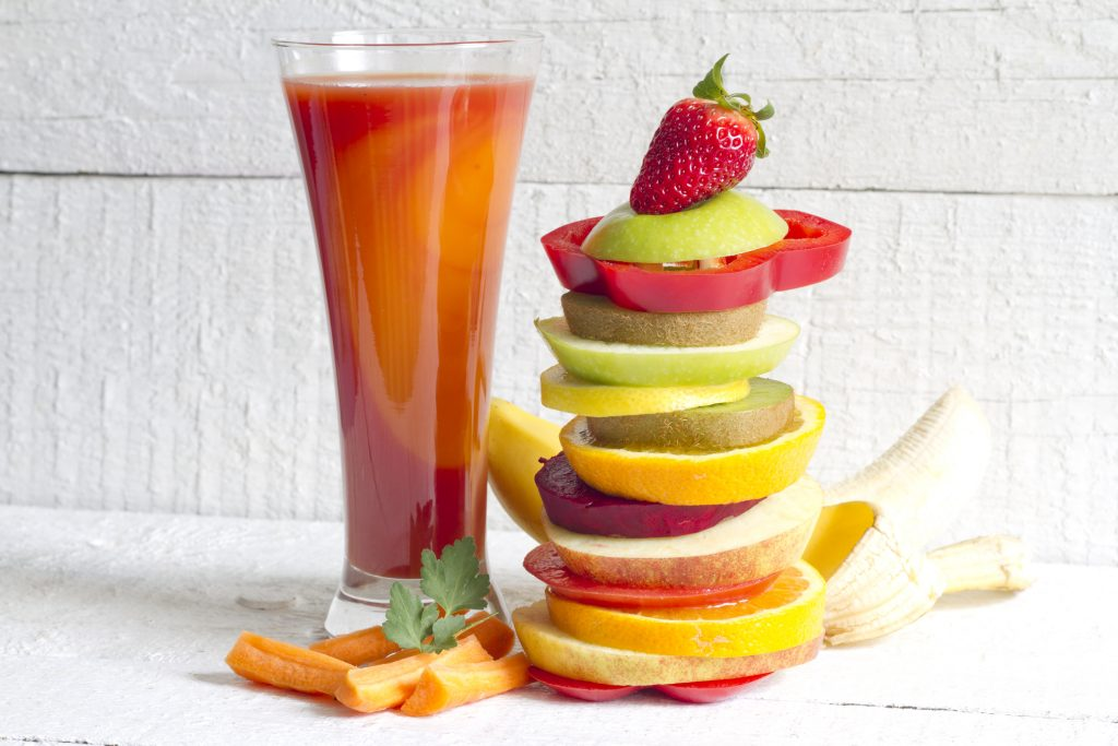 Smoothie made with fruit and vegetables plus a pile of fruit